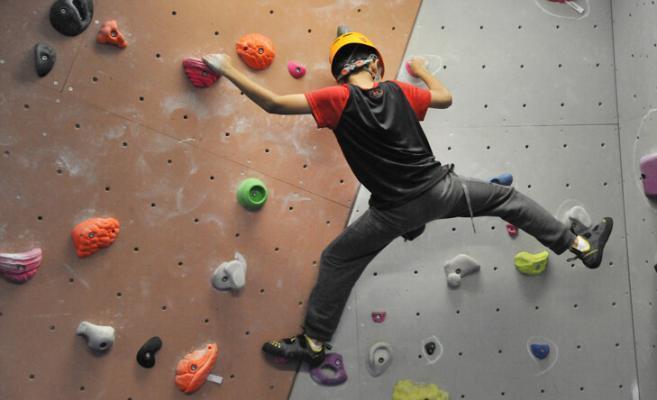 boy climbing n bouldering wall