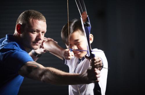 instructor helping boy aim bow and arrow
