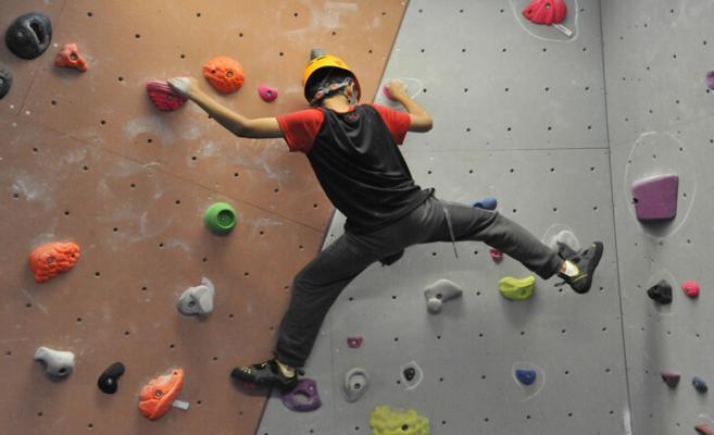 teenage boy climbing on a bouldering wall